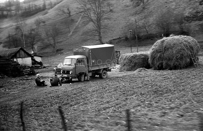 BOSNIA-HERZEGOVINA, Belgrade-Sarajevo Road, 03/2003..Lanscape pictures taken from the bus between Belgrad and Sarajevo. .Peasants near the village of Zaklopaca.  .BOSNIE-HERZEGONVINE, Route Belgrade-Sarajevo, 03/2003..Photo prise depuis le bus qui relie Belgrade à Sarajevo. Des paysans en train de réparer un camion près du village de Zaklopaca..© Bruno Cogez