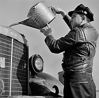 Melvin Cash, truck driver, putting water in his radiator along U.S. Highway 29 in North Carolina enroute to Charlotte. March 1943.<br /> <br /> Photo by John Vachon.