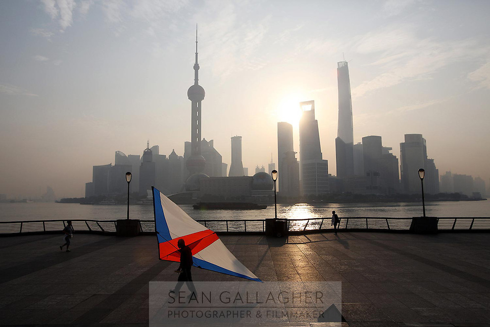 A man carries a large kite kite at sunrise in front of the distinctive Pudong skyline, 2014.<br /> <br /> To license this image, please contact the National Geographic Creative Collection:<br /> <br /> Image ID: 2169163 <br /> <br /> Email: natgeocreative@ngs.org<br /> <br /> Telephone: 202 857 7537 / Toll Free 800 434 2244<br /> <br /> National Geographic Creative<br /> 1145 17th St NW, Washington DC 20036
