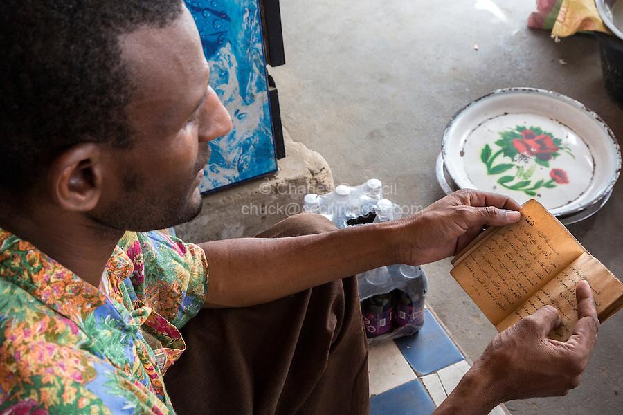 Senegal, Saint Louis.  A Pular Senegalese Shopkeeper from the Fouta Jalon region, reading an Islamic prayer book while waiting for a customer.