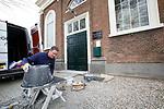 Foto: VidiPhoto<br /> <br /> HETEREN – Tegelzetter Rob Pater uit het Brabantse Wilbertsoord plaatst maandag een nieuwe vloer in de Hervormde kerk in het Gelderse Heteren. De keramische hardstenen tegels vervangen de tapijttegels uit de jaren zestig, die al lange tijd aan vervanging toe waren. Een aannemer uit de gemeente verrichtte al eerder samen met vrijwilligers het voorwerk, door een nieuwe betonnen vloer te storten. Eind deze week moet de nieuwe vloer er in liggen. Om alles precies op maat te krijgen rond de monumentale kansel vereist nogal wat meet- en slijpwerk. In de kerk worden als sinds de tweede lockdown oktober vorig jaar geen diensten gehouden met kerkgangers vanwege de coronamaatregelen. De werkzaamheden in de kerk zorgen dan ook niet voor veel overlast. De Hervormde gemeente van Heteren telt op papier zo'n 500 leden, van wie zo'n 200 personen kerkelijk meelevend zijn. Van een krimp zoals in veel PKN-gemeenten is volgens ouderling Wessel van Binsbergen geen sprake. Het kerkgebouw dateert uit 1838.