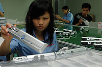 Workers inspect freshly moulded and painted parts of a computer casing in Shenzhen, China. This factory makes housing for computers, DVD's, mobile phones and computer mouses..