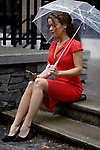 Young woman in a red elegant dress sitting on the stairs with an umbrella in the rain on a city street with a phone in her hand