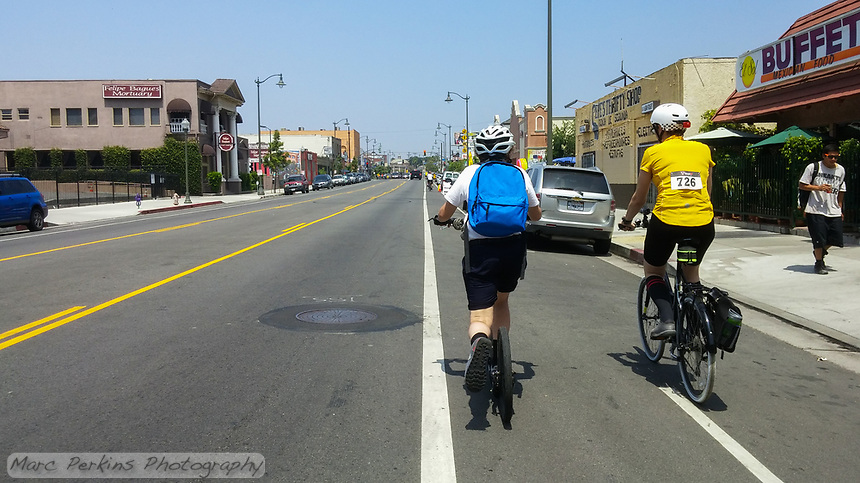 Holland, on his Yedoo kick scooter, and Michelle, on her Terry Burlington city bike, ride in the bike lane on 1st street in Los Angeles in this street-photography style shot.  A young man walks down the street in front of the El Sol Mexican Food buffet restaurant. Taken during the 2017 (17th annual) Los Angeles River Ride.