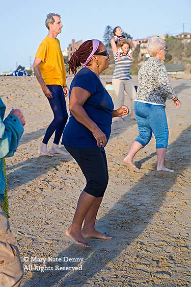 Black mature female works out with exercise dance class on Playa del Rey Beach in Los Angeles, CA