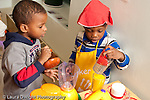 Education preschool 3-4 year olds pretend play two boys in kitchen area one wearing a hat playing together with glasses and containers horizontal