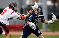 Jake Bernhardt (3) of Maryland checks Rob Fitzpatrick (15) of Penn at Ludwig Field in College Park, Maryland.