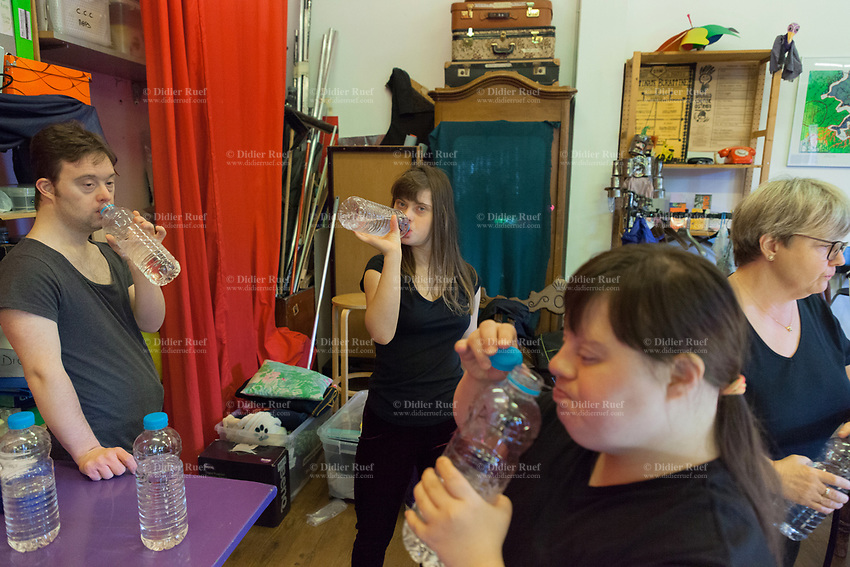 Switzerland. Canton Ticino. Locarno. Fauni Theater.  MOPS_DanceSyndrome is an independent Swiss artistic, cultural and social organisation operating in the field of contemporary dance and disability. It is composed only of Down dancers. Break time for dancers;  Simone Lunardi (L), Gaia Mereu (C) and Amedea Aloisi (R) are all drinking water in plastic bottles. The elderly woman, Manuela Viecelli (MOPS dancers' assistant) works as staff for MOPS_DanceSyndrome. Down syndrome (DS or DNS), also known as trisomy 21, is a genetic disorder caused by the presence of all or part of a third copy of chromosome 21 It is usually associated with physical growth delays, mild to moderate intellectual disability, and characteristic facial features. 5.12.2019 © 2019 Didier Ruef