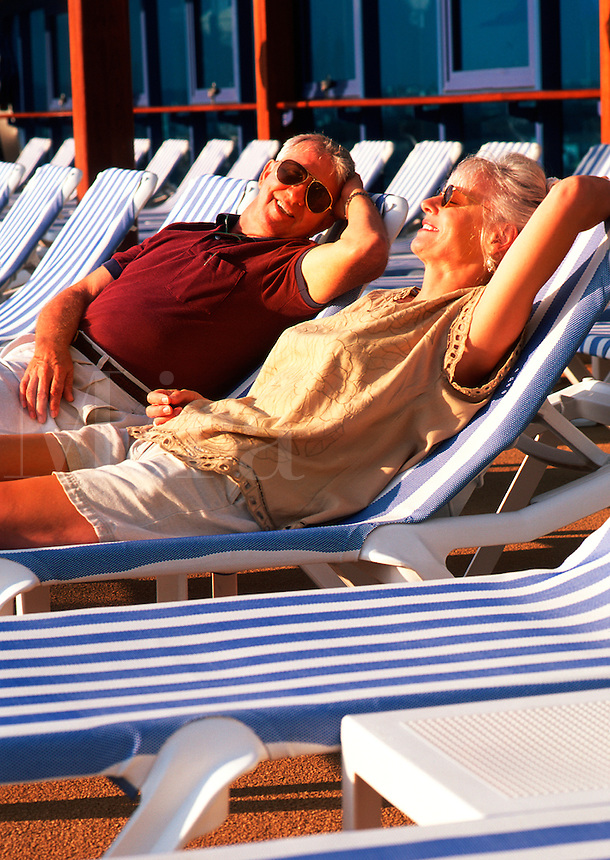Retired couple on cruise ship, relaxing in deck chairs
