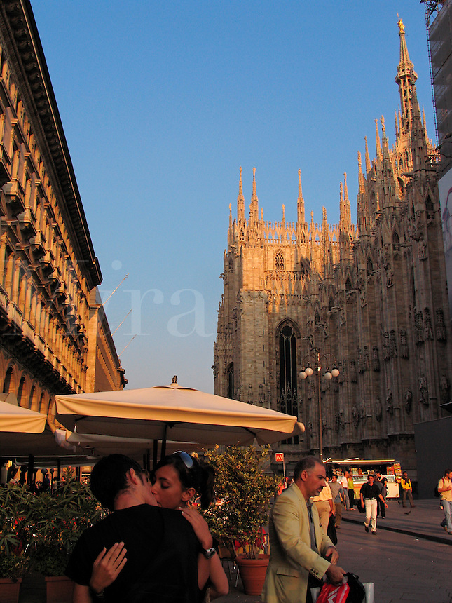 Italian couple kissing near cafe at Galleria Vittorio Emanuele wht the Duomo in background, Milan, Italy - no model release availabl