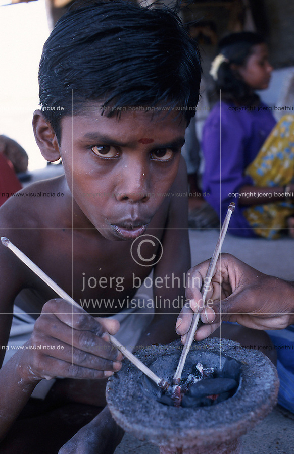 INDIA Tamil Nadu, Karur, child labour, boy work in a polishing unit for artificial synthetic gems, he is putting the stones on bamboo sticks with wax before polishing / INDIEN, Kinderarbeit, Junge arbeitet in einer kleinen Edelsteinschleiferei im Dorf V. Pudur bei Karur, hier werden Halbedelsteine und kuenstliche Edelsteine poliert