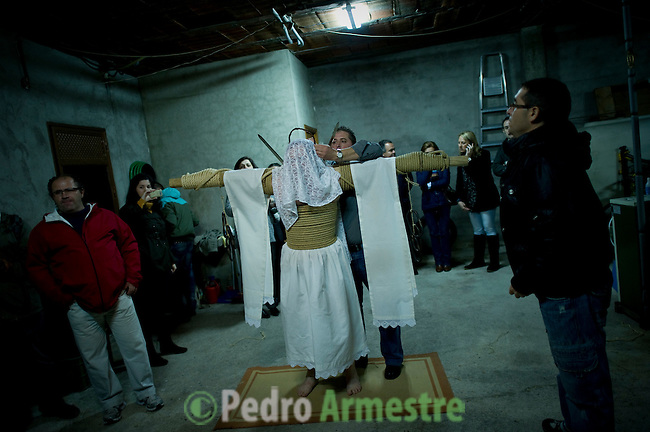 A man attached to a cross, an 'Empalao' penitent, gets dressd by a relative before walking the 14 stations of the cross or 'Via Crucis', a depiction of the final hours of Jesus Christ. Empalaos make the steps of the 'Via Crucis', marking the Stations of the Cross, during the night of Maundy Thursday while bound by rope to a crucifix as an act of penance and to honour a promise made to the Empalaos Brotherhood and the Christ of Vera Cruz, in the town of Valverde de la Vera. The process of dressing the Empalao in the traditional costume is taken with great care, with the family and dressers paying attention to ensure that no harm is caused to the penitent and that they are aided in their recovery, including being massaged and rubbed with rosemary alcohol. Many Spanish towns and villages retain such rites and religious traditions, many passed down from medieval times, across the Easter weekend. (c) Pedro ARMESTRE