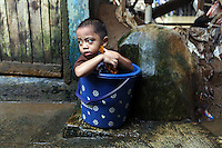 A child sits in a bucket while taking a bath in the slums of central Jakarta.<br /> <br /> To license this image, please contact the National Geographic Creative Collection:<br /> <br /> Image ID: 1588034 <br />  <br /> Email: natgeocreative@ngs.org<br /> <br /> Telephone: 202 857 7537 / Toll Free 800 434 2244<br /> <br /> National Geographic Creative<br /> 1145 17th St NW, Washington DC 20036