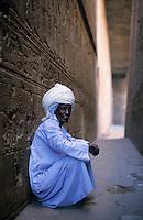 Man sitting against a wall at the Temple of Edfu, Edfu, Egypt.