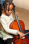 Education K-8 private public partnership girl playing cello during school day age 6