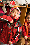 Education Preschool 3-4 year olds fine motor skills boy zipping own coat vertical