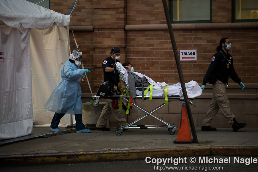 Medical workers wheel a patient out of a triage tent to the emergency room at Maimonides Medical Center on March 28, 2020 in Brooklyn, NY.  NYC's daily death toll from the coronavirus nearly tripled from the previous 24-hour period from 85 on Friday to 222 on Saturday.  Photograph by Michael Nagle/Redux