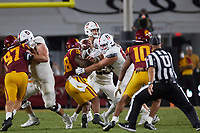 LOS ANGELES, CA - SEPTEMBER 11: Tanner McKee #18 of the Stanford Cardinal looks to pass the ball with protection from Drake Nugent #60 and Branson Bragg #66 during a game between University of Southern California and Stanford Football at Los Angeles Memorial Coliseum on September 11, 2021 in Los Angeles, California.