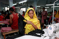 A child labourer making garments in a textiles factory. Most of the workers in this factory are children.