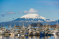 Float plane approaches Sitka Channel, commercial fishing boats in New Thomsen harbor, Sitka, Alaska. Inactive volcano, Mount Edgecumbe on Kruzof Island in the distance.