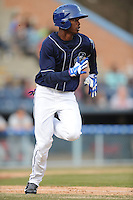 Asheville Tourists left fielder Raimel Tapia #15 runs to first during a game against the Delmarva Shorebirds at McCormick Field on April 5, 2014 in Asheville, North Carolina. The Tourists defeated the Shorebirds 5-3. (Tony Farlow/Four Seam Images)