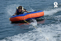 Boy (11-13) riding inflatable being towed in water (Licence this image exclusively with Getty: http://www.gettyimages.com/detail/200482344-001 )