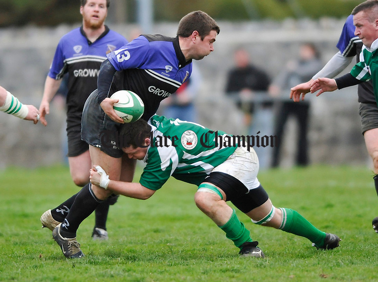 Kilrush's Andrew O Neill is tackled by Richmond's Dennis Russell  during the Webb Cup final at Ennis RFC grounds. Photograph by John Kelly.