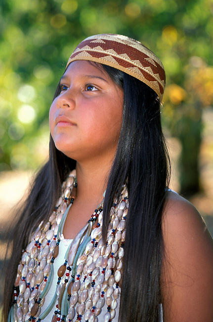 Close-up shot of a traditional Yurok girl; (11yrs old); wearing a traditional multi-strand beaded shell necklaces and a basket woven hat. Hoopa Valley Indian Reservation California