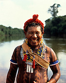 Xingu, Brazil. Kakuyi, a Kayapo man, smiling with body paint, amulets and necklaces; river behind. A-Ukre Village.