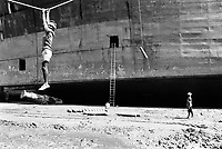 India. Province of Gujarat. Alang. Workers, all men, draw  oxygen tanks for welding from the beach up to the ship. A worker flies in the air and holds himself tight with both hands on a rope. Ship aground. Vessel stranded. Bottoms of ship at low tide on the shore. Alang, located in the Gulf of Khambhat, is a ships breaking place. Alang is considered as the biggest scrapyard in the world. Ships recycling for its metals. Environmental issues. Hazardous waste. © 1992 Didier Ruef