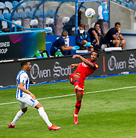 Wigan Athletic's Nathan Byrne clears a ball under pressure from Huddersfield Town's Danny Simpson<br /> <br /> Photographer Alex Dodd/CameraSport<br /> <br /> The EFL Sky Bet Championship - Huddersfield Town v Wigan Athletic - Saturday 20th June 2020 - John Smith's Stadium - Huddersfield <br /> <br /> World Copyright © 2020 CameraSport. All rights reserved. 43 Linden Ave. Countesthorpe. Leicester. England. LE8 5PG - Tel: +44 (0) 116 277 4147 - admin@camerasport.com - www.camerasport.com