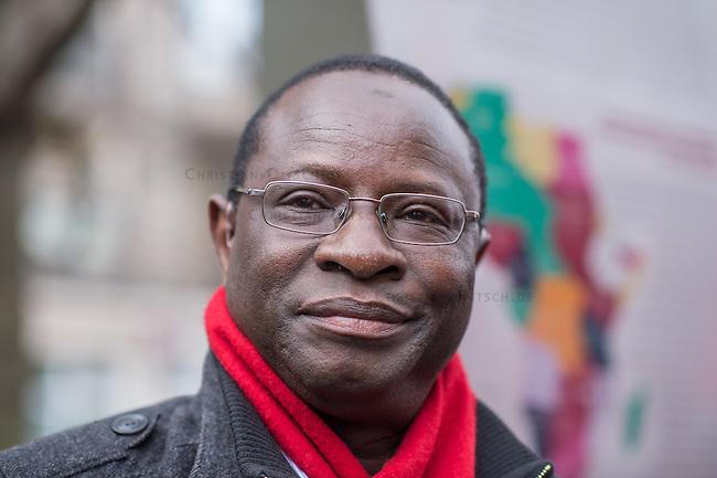 """Etwa 200 bis 250 Menschen beteiligten sich am Samstag den 28. Februar 2015 zum Jahrestag der sog. """"Berliner Afrika-Konferenz"""" an einem Gedenkmarsch in Erinnerung an die Opfer des Kolonialismus, des Sklavenhandels und der Ausbeutung Afrkias durch die Europaeischen Staaten. Sie forderten eine Entschuldigung der Bundesregierung fuer die in deutschem Namen begangenen Verbrechen in den deutschen Afrika-Kolionien, eine Entschaedigung der Angehoerigen der Opfer und die sofortige Rueckgabe der aus Namibia verschleppten Schaedel von Anfuehrern des Volksgruppen der Nama und Herero.<br /> Im Bild: Karamba Diaby (51) aus Halle an der Saale, erster aus Afrika stammender Abgeordneter im Deutschen Bundestag. Diaby Mitglied der SPD-Fraktion.<br /> 28.2.2015, Berlin<br /> Copyright: Christian-Ditsch.de<br /> [Inhaltsveraendernde Manipulation des Fotos nur nach ausdruecklicher Genehmigung des Fotografen. Vereinbarungen ueber Abtretung von Persoenlichkeitsrechten/Model Release der abgebildeten Person/Personen liegen nicht vor. NO MODEL RELEASE! Nur fuer Redaktionelle Zwecke. Don't publish without copyright Christian-Ditsch.de, Veroeffentlichung nur mit Fotografennennung, sowie gegen Honorar, MwSt. und Beleg. Konto: I N G - D i B a, IBAN DE58500105175400192269, BIC INGDDEFFXXX, Kontakt: post@christian-ditsch.de<br /> Bei der Bearbeitung der Dateiinformationen darf die Urheberkennzeichnung in den EXIF- und  IPTC-Daten nicht entfernt werden, diese sind in digitalen Medien nach §95c UrhG rechtlich geschuetzt. Der Urhebervermerk wird gemaess §13 UrhG verlangt.]"""