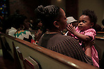 CHARLOTTE, NC - NOVEMBER 2:  Cheresa Tucker (cq Cheresa) and her 16-month-old daughter Jurnee Tucker (cq Jurnee) pray at St. Paul Baptist Church in Charlotte, NC, on Sunday, November 2, 2014, after hearing a sermon by Rev. William Barber II,  president of the North Carolina NAACP.  Barber has been instrumental as an activist for voter rights.  Cheresa Tucker said she voted early and will assist others on election day Tuesday in Charlotte.  (Photo by Ted Richardson/For The Washington Post)