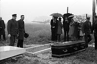 21 avril 1972. Au 1er plan cercueil de Didier Daurat posé à côté du caveau ; au 2nd plan vue de face de la famille et des amis autour du caveau, parapluies ; en arrière-plan avions sur la piste de Montaudran, brouillard, pluie. Cliché pris lors de la cérémonie organisée dans le cadre du transfert du corps de Didier Daurat dans un caveau en bordure de la piste de Montaudran.