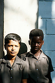 Lusaka, Zambia; two boys in uniform shirts, one black, one of mixed race.