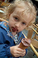 Little girl eating a chocolate ice cream cone and getting most of it on her face, Paris, France.