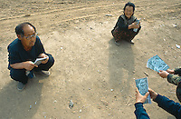 China. Province of Jilin. Li Shu Gou village. A worker, dressed in military clothes, from the Forestry Department distributes to the population leaflets on Siberia Tiger from the Hunchun Nature Reserve. People talk together, kneeling down in a traditional chinese way. © 2004 Didier Ruef