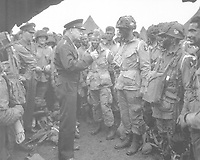 """Gen. Dwight D. Eisenhower gives the order of the Day.  """"Full victory-nothing else"""" to paratroopers in England, just before they board their airplanes to participate in the first assault in the invasion of the continent of Europe.  June 6, 1944.  Moore. (Army)  <br /> NARA FILE #:  111-SC-194399<br /> WAR & CONFLICT BOOK #:  1040"""