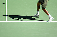 A shadow of a man playing tennis.