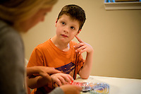 """Jack Ursitti, age 7, works on a learning activity with his teacher Sarah Hoey, of the Nashoba Learning Group, in his home in Dover, Mass., on Monday, July 25, 2011.  Hoey has been working with Jack since he was 3. """"He was completely non-verbal when I met him,"""" she said. Now Jack can spell basic words and speak at a basic level...Jack has been diagnosed with autism.  After school at his home, Jack works with his teacher and a therapist to do educational and independent leisure activities. ..Hoey spends 1 or 2 days a week after school with Jack...Jack Ursitti wears a small GPS ankle bracelet at all times in case he runs off from his family or caretakers. The device will be activated if he goes missing, allowing police and other searchers to find him."""