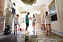 Tulane student Chase Kelly helps Delaney Connor <br /> and others paint a living room while volunteering with South Seventh Ward Neighbors, 2016.