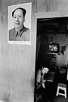 China. Province of Guangdong. The village of Beilin is part of the town of Guiyu. A woman, working in a public phone shop, smiles to a customer. A poster of the chairman Mao Zedong is on the wall. © 2004 Didier Ruef .