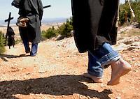 IRUNBERRI - LUMBIER, NAVARRE JUNE 11: Barefoot penitents dressed in black monks habits carry heavy crosses during the celebration of the 'Cruceros' brotherhood penitential pilgrimage to the 'Ermita de la Trinidad' on June 11, 2006 in Irunberri - Lumbier, Navarre. Photo by Ander Gillenea