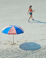 A woman dials a cell phone as she walks along a beach at Virginia Beach, Va.