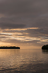 Russell Islands, Solomon Islands; a sunset sky reflects in the calm waters of a secluded bay, rendering the remote tropical islands in silhouette