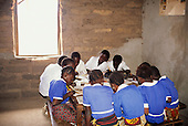 The Gambia. Schoolchildren sitting round a table in a mud brick school room working at their exercise books.