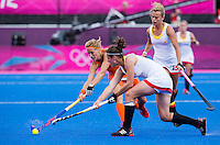 29 JUL 2012 - LONDON, GBR - Carlien Dirkse van den Heuvel (NED) of The Netherlands (left) beats Louise Cavenaile (BEL) of Belgium (second from left) to the ball during the women's London 2012 Olympic Games Preliminary round hockey match at the Riverbank Arena in the Olympic Park in Stratford, London, Great Britain .(PHOTO (C) 2012 NIGEL FARROW)