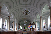 St Michael and All Angels church, attached to the house, its light white and pale green interior decorated with restrained plasterwork friezes and plain columns. It was built in 1785 by Charles Evans