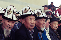 Kyrgyz men watching horse races in a village outside of the capital, Bishkek. They are seen wearing the Kalpak, a traditional high-crowned hat made of felt.
