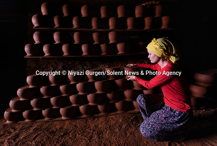 """A woman arranges handmade clay pottery after being taken out of the furnace. The furnace where the pottery is placed is two metres deep and used to fire treat the clay to make it hard and durable. The pots are made in the city of Aydin, Turkey, and once they finished, they are sold within the country and overseas for anywhere between 20 to 100 US Dollars.Teacher Niyazi Gürgen said when asked what he thought about his images: """"I was very excited while taking these photos. The colors and light are great. It was an unforgettable moment for me.""""<br /> <br /> Please byline: Niyazi Gurgen/Solent News<br /> <br /> © Niyazi Gurgen/Solent News & Photo Agency<br /> UK +44 (0) 2380 458800"""